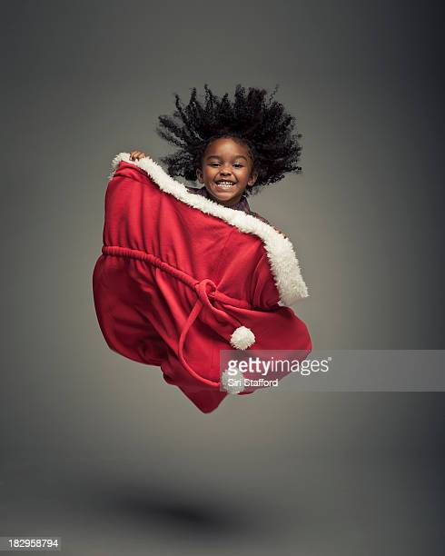 Young girl jumping in extra large Santa Bag