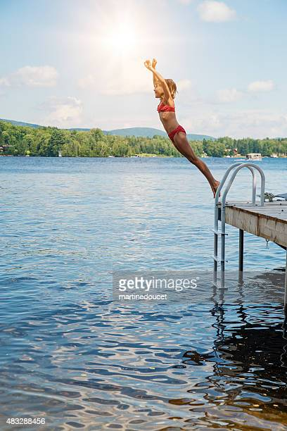 Young girl jumping in lake from pier on sunny day.