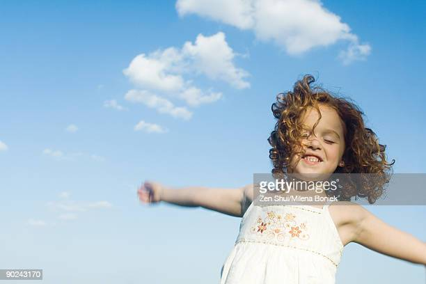 Young girl jumping in the air, arms outstretched, eyes closed, waist up