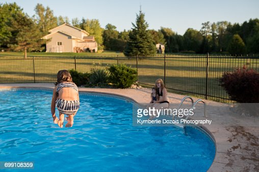 Young Girl Jumping Into Swimming Pool Rear View Stock Photo Getty Images
