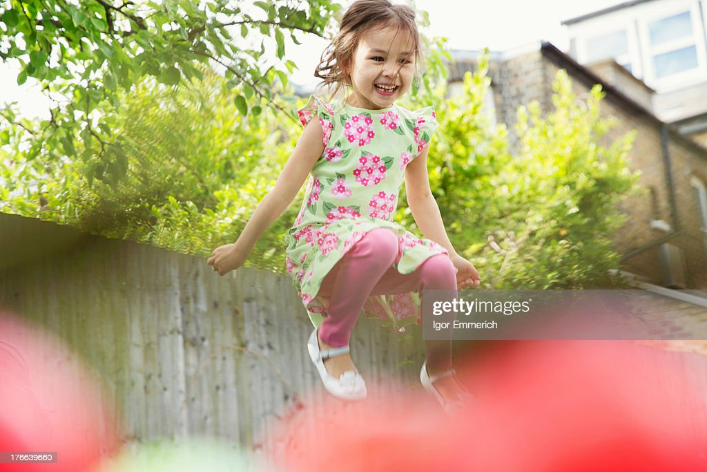 Young girl jumping mid air in garden