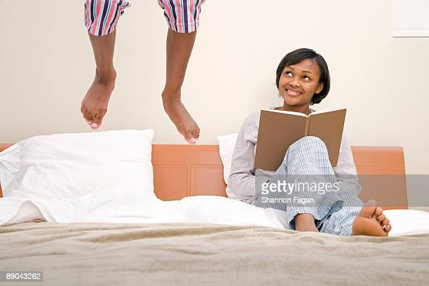 Young Girl Jumping on Bed with Mother Reading Book