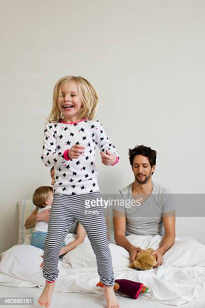 Young girl jumping on her parents bed