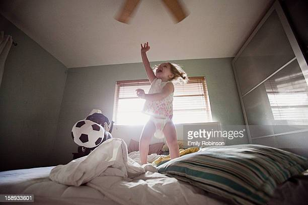 Young girl jumping on the bed with a dog