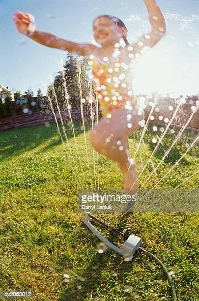 Young Girl Jumping Through a Garden Sprinkler