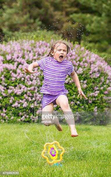 Young Girl Jumping Through Sprinkler on Summer Day