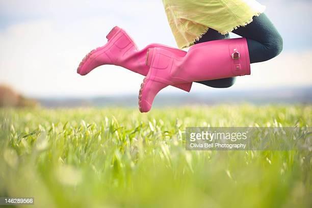 Young girl jumping with pink boots
