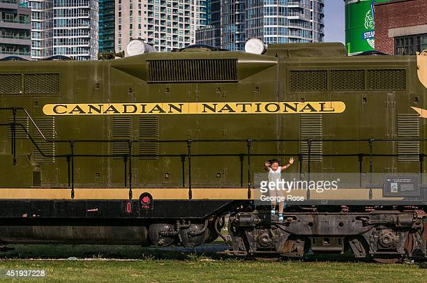 A young girl jumps off a diesel train locomotive parked at The Roundhouse on June 28 2014 in Toronto Ontario Canada Canada's most populous city is...
