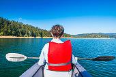 Strong young girl kayaking on the Lokvarsko lake in Gorski kotar, Croatia. Active girl having enjoying adventurous experience on a sunny day.