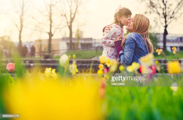 Young girl kissing her mother in flowers outdoors