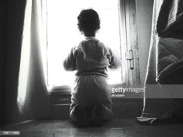 Giovane ragazza in ginocchio mentre guardando fuori la finestra, bianco e nero