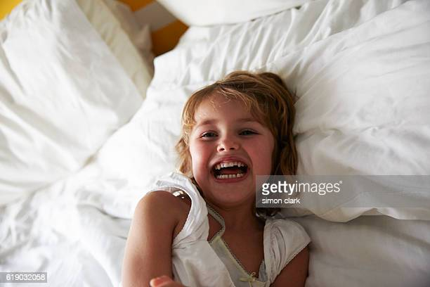 young girl laughing on bed