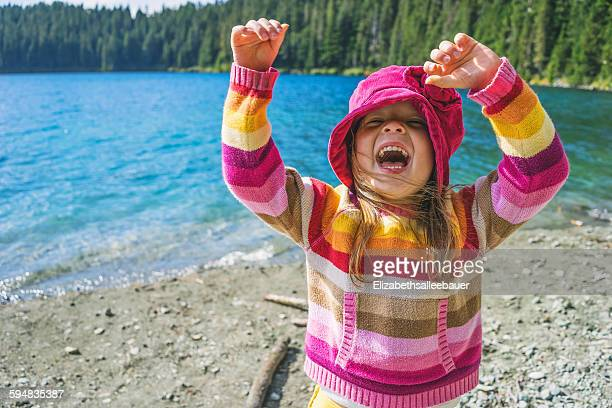 Young girl laughing with her arms in the air
