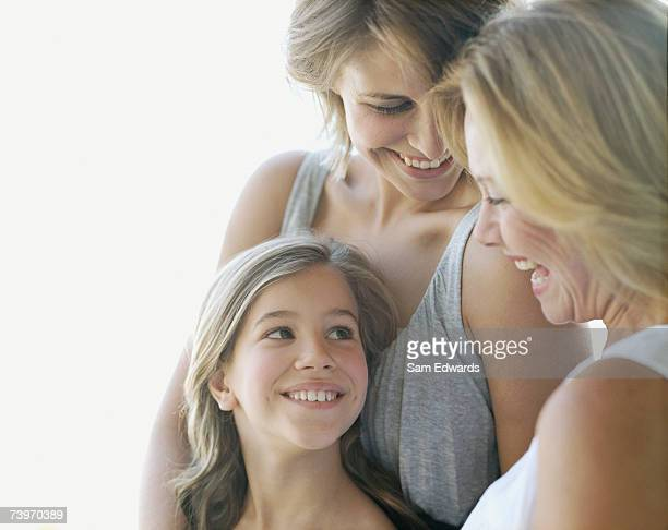Young girl laughing with mother and grandmother