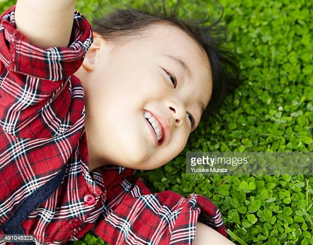 Young girl laying in the green grass