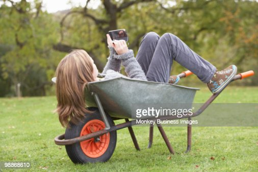 Young Girl Laying Wheelbarrow Using Smart Mobile Phone : Stock Photo