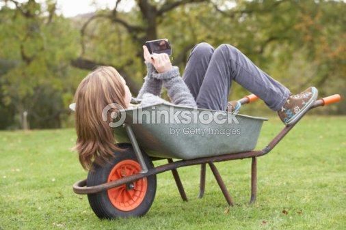 Young Girl Laying Wheelbarrow Using Smart Mobile Phone : Stock Photo