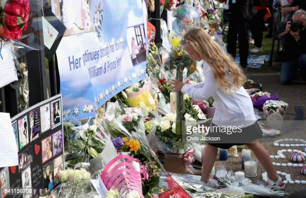 A young girl lays flowers at the Gates of Kensington Palace on the 20th anniversary of the death of Princess Diana at Kensington Palace on August 31...
