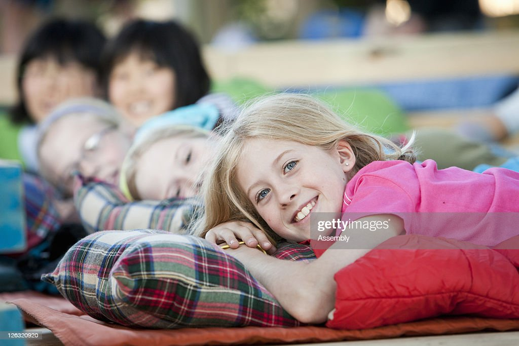 Young girl lays in sleeping bag next to friends : Stock Photo