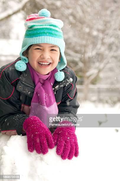 Giovane donna appoggiato su una grande palla di neve nel cortile anteriore