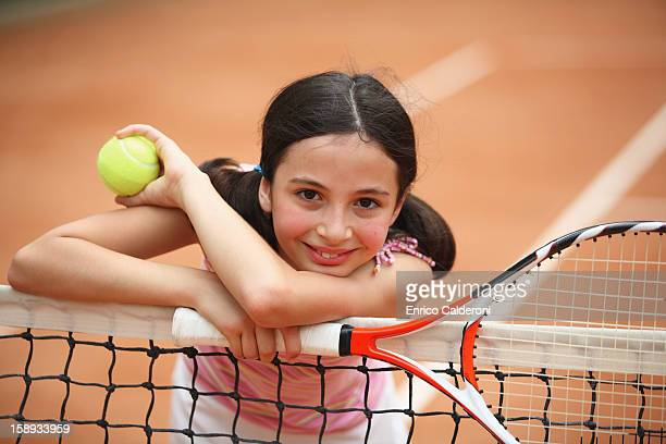Young Girl Leaning On Net In Tennis Court