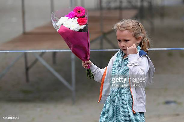 A young girl leaves flowers in Market Square Birstall after Jo Cox Labour MP for Batley and Spen was shot and stabbed yesterday by an attacker at her...