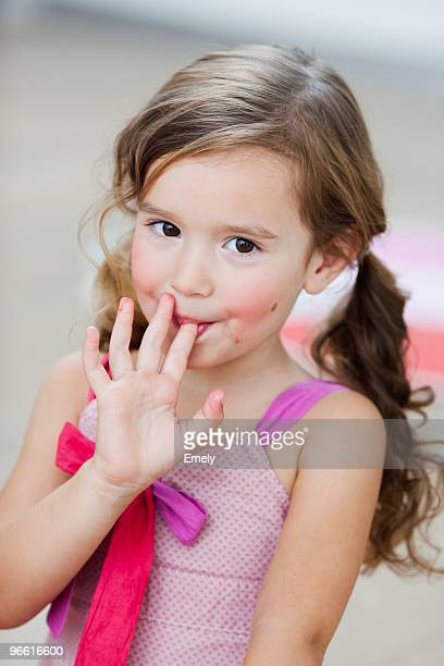 young girl licking her fingers