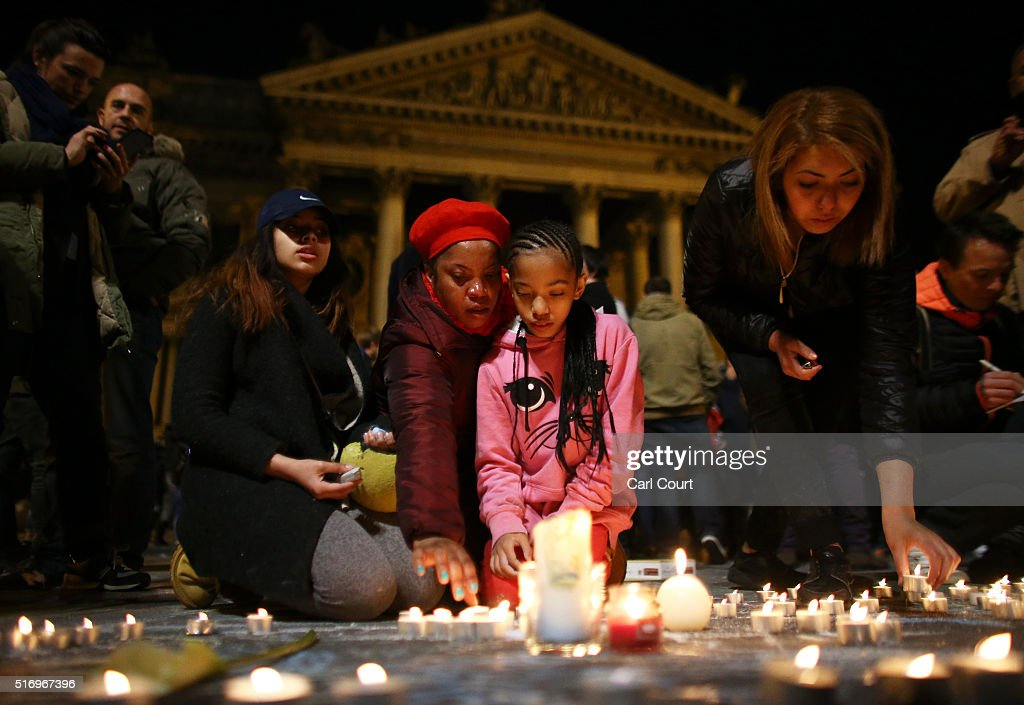 A young girl lights a candle at the Place de la Bourse following today's attacks on March 22 2016 in Brussels Belgium At least 31 people are thought...