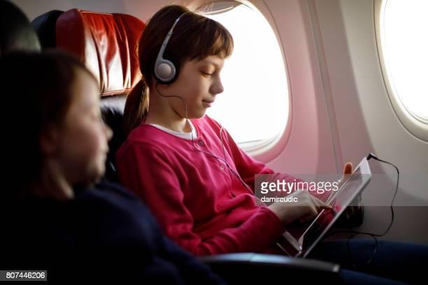 Junges Mädchen Musik hören im Flugzeug