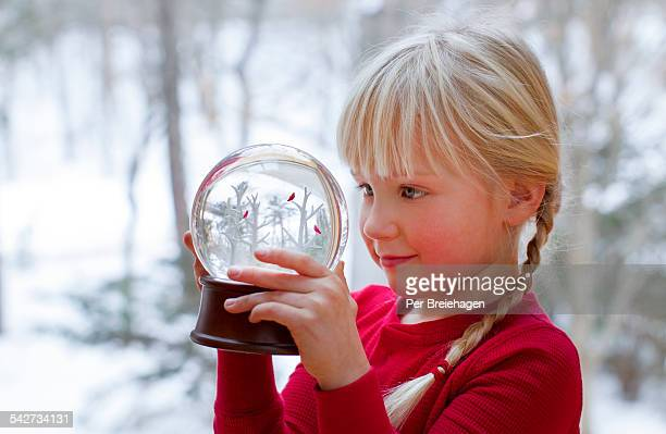 A young girl looking at a snow globe