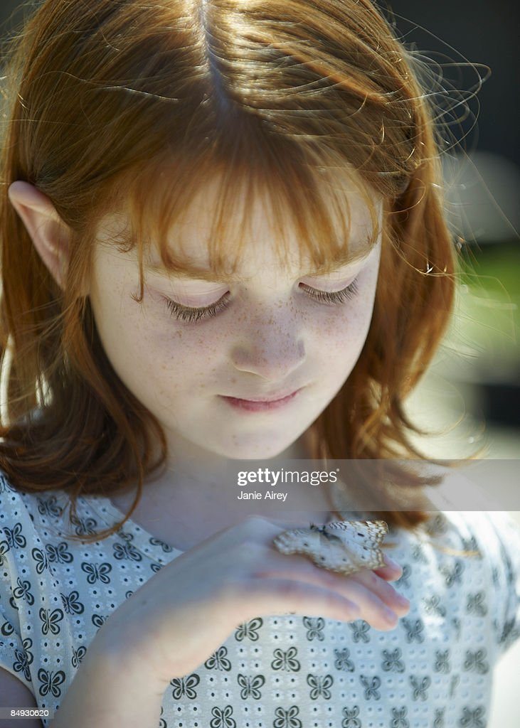 Young girl looking at butterfly : Stock Photo