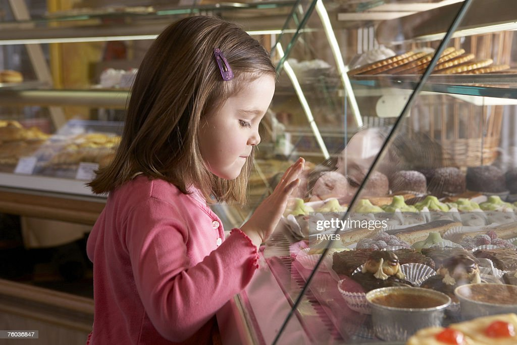 Young girl (9-11) looking at cakes in display cabinets, side view : Stock-Foto