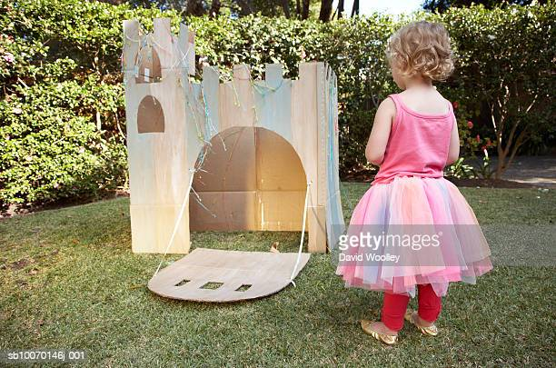 Young girl (12-17 months) looking at cardboard castle in garden