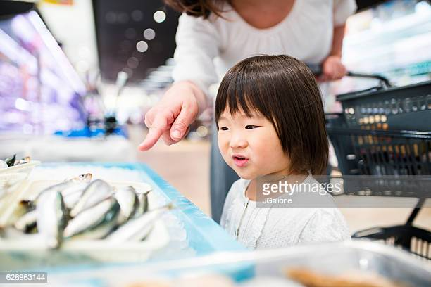Young girl looking at fish in a supermarket