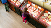 A young girl peers into the displays looking at the exhibits in a museum