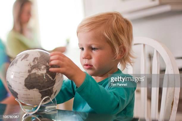 Young girl looking at globe