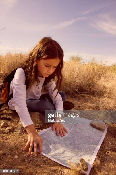 Young Girl Looking At Map In Desert