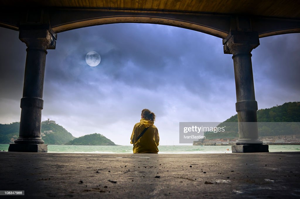 Young girl looking at the moon in Donostia : Stock Photo
