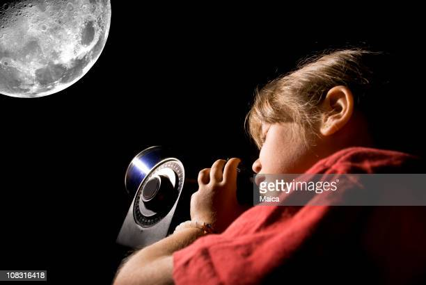 Young girl looking at the moon through an electronic telescope