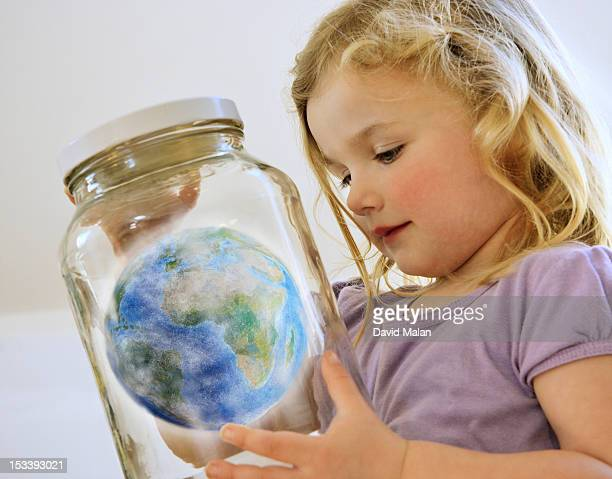 young girl looking at the world in a jar.