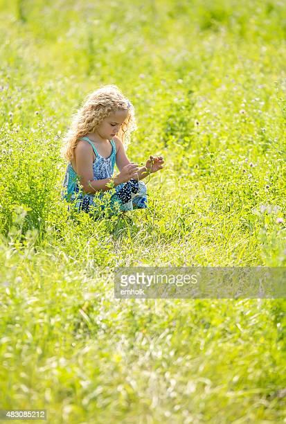 Jeune fille à la recherche sur les fleurs sauvages dans la lumière du matin