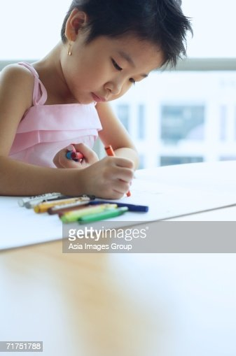Young girl looking down drawing with crayons stock photo for How to draw a girl looking down