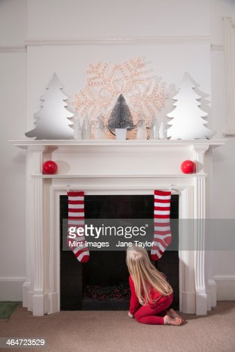 A young girl looking expectantly up the chimney awaiting the arrival of Father Christmas.