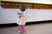 Young girl looking for her name in a school hall