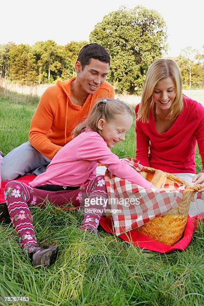 A young girl looking for something in a picnic basket, her parents look on.