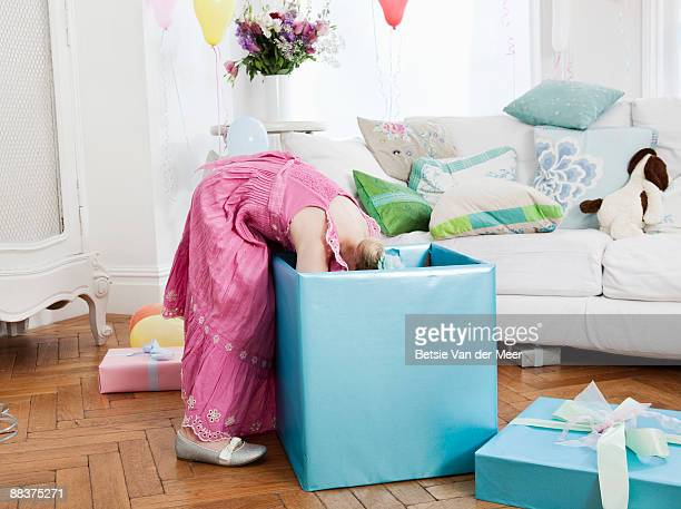 Young girl looking into large present