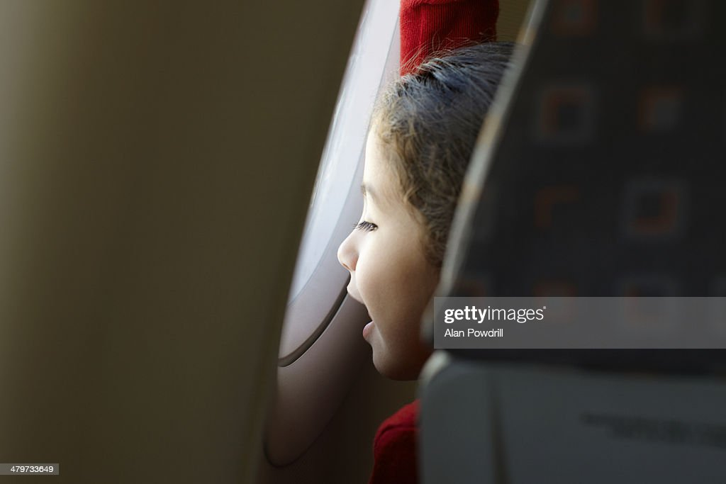 Young girl looking out airplane window