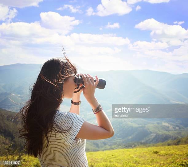 Chica joven mirando a través de binoculares