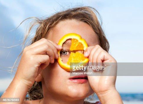 Young girl looking through slice of orange : Stock Photo