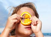 Young girl looking through slice of orange